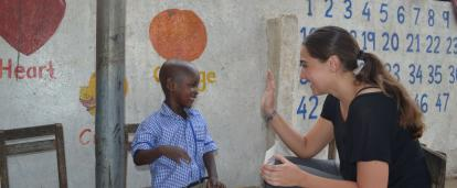 A Childcare volunteer in Ghana offers a child a high five for successfully completing an educational task.
